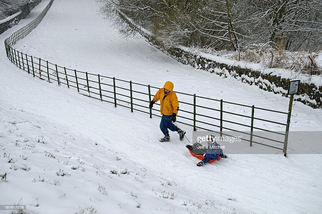 A man pulls a boy on a sledge during recent snowfall on February 13, 2013 in Blanefield, Scotland. Weather forecaster have issued a yellow weather warning of up to 10cm of snow on higher routes, with the possibility of travel disruption.