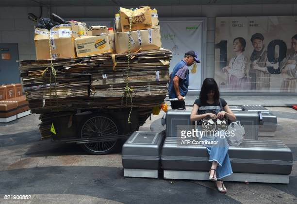 TOPSHOT A man pulls a cart filled with cardboard boxes at a shopping district in Seoul on July 25 2017 South Korea's economy is set to grow at its...