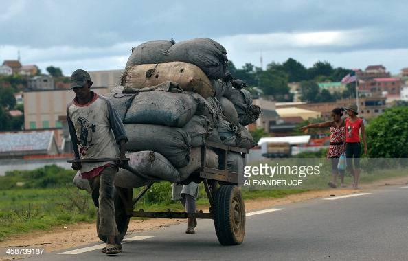 A man pulls a cart full of charcoal bags in Antananarivo on December 21 a day after the elections for a new President in a runoff vote aimed at...