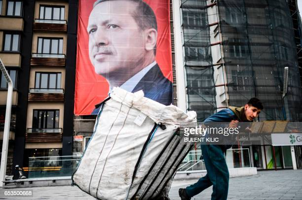 TOPSHOT A man pulls a cart in front of a huge portrait of Turkish President Recep Tayyip Erdogan on Taksim Square in Istanbul on March 15 2017 Turkey...