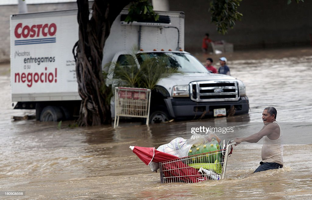 A man pulls a cart with supplies through a flooded street in Acapulco, state of Guerrero, Mexico, on September 17, 2013 as heavy rains hit the country. Mexican authorities scrambled Tuesday to launch an air lift to evacuate tens of thousands of tourists stranded amid floods in the resort of Acapulco following a pair of deadly storms. The official death toll rose to 47 after the tropical storms, Ingrid and Manuel, swarmed large swaths of the country during a three-day holiday weekend, sparking landslides and causing rivers to overflow in several states.