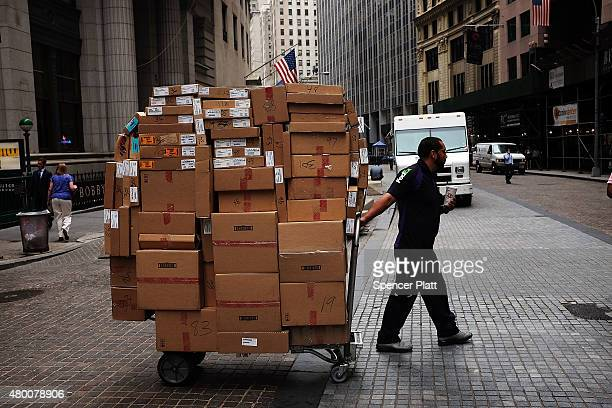 A man pulls a cartload of packages for delivery in the financial district on July 9 2015 in New York City The International Monetary Fund announced...