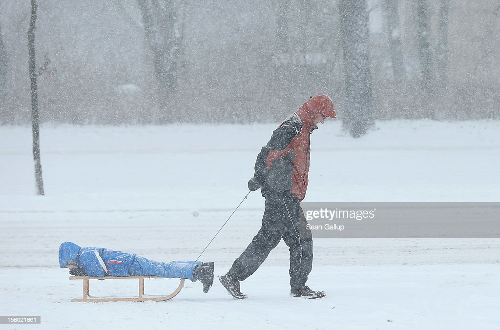 A man pulls a child on a sled along a snow-covered sidewalk during a heavy snowfall in Zehlendorf district on December 9, 2012 in Berlin, Germany. Northeastern Germany was inundated with snow that covered highways and blanketed the region.