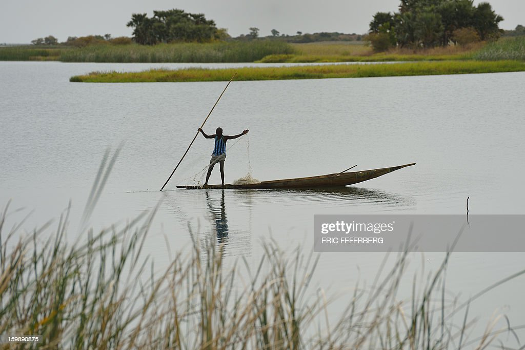 A man pulls a fishing net as he crosses the Niger river in a boat on January 22, 2013 near Segou, 240km North of Bamako. Mali's army chief today said his French-backed forces could reclaim the northern towns of Gao and fabled Timbuktu from Islamists in a month, as the United States began airlifting French troops to Mali.
