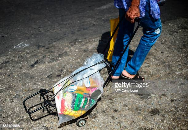 A man pulls a mobile travel cart loaded with a bag of foodstuff as he leaves one of the food distribution centers called CLAP which are run by...