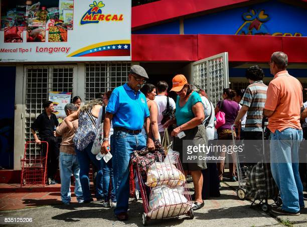 A man pulls a mobile travel cart loaded with bags of foodstuff as he leaves one of the food distribution centers called CLAP which are run by...