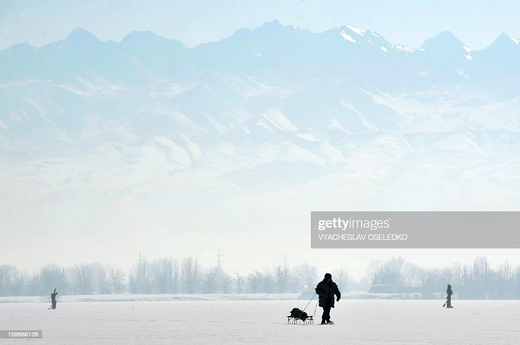 A man pulls a sled on the ice of a frozen lake in front of the Tien Shan mountains outside Bishkek on January 18, 2013.