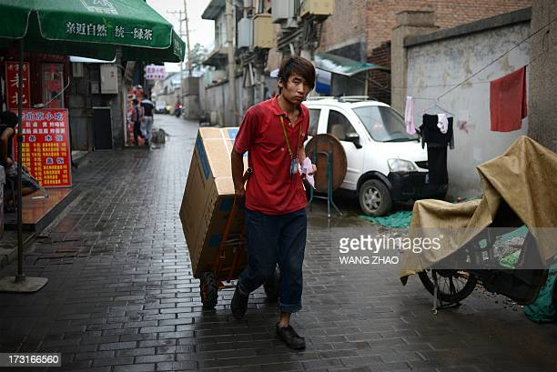 A man pulls goods on a trolley outside a restaurant at a alley in Beijing on July 9 2013 China's annual inflation accelerated to 27 percent in June...