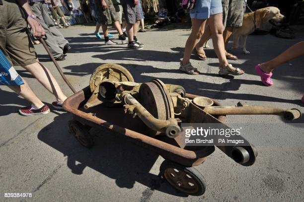 A man pulls his Radio Flyer American style children's trolley filled with secondhand rear suspension and wheel hub parts for a VW Baywindow Type 2...