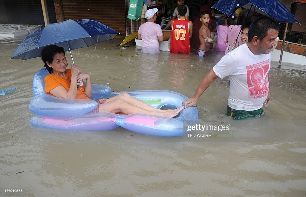 A man pulls his wife in an inflatable boat as they buy food at a submerged market in Cavite, southwest of Manila on August 19, 2013. Torrential rain paralysed large parts of the Philippine capital August 19, as neck-deep water swept through homes, while floods in northern farming areas claimed at least one life.