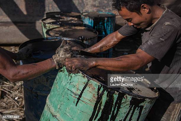 A man pulls on a heavy oil drum on the banks of the Irrawaddy River on December 16 2013 in Yangon Myanmar Large cargo ships on the Irrawaddy River in...