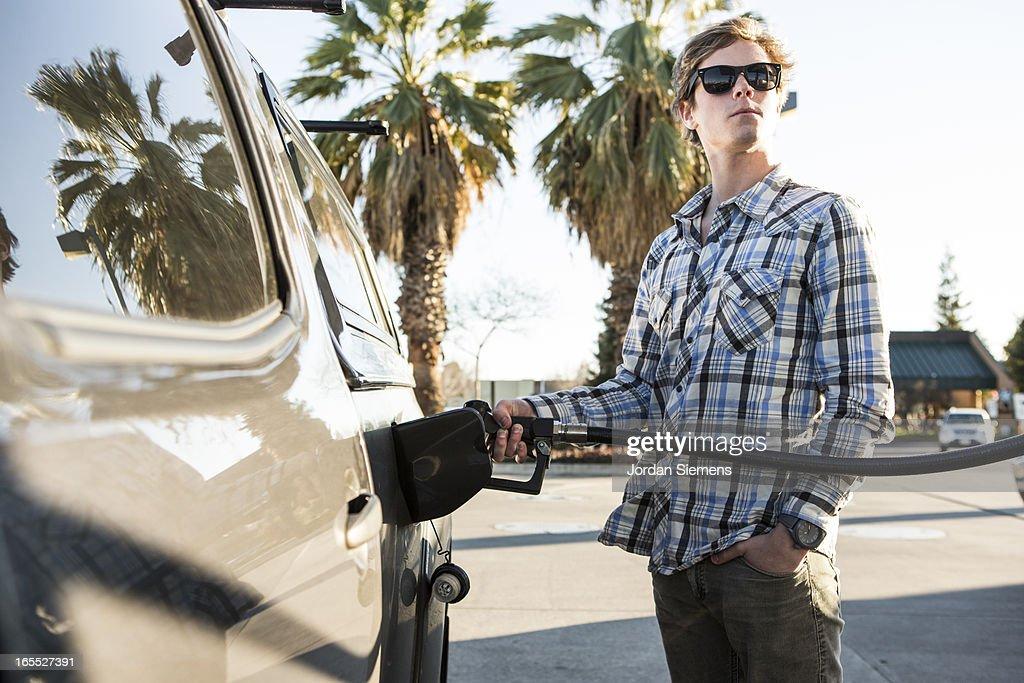 A man pumping gas.