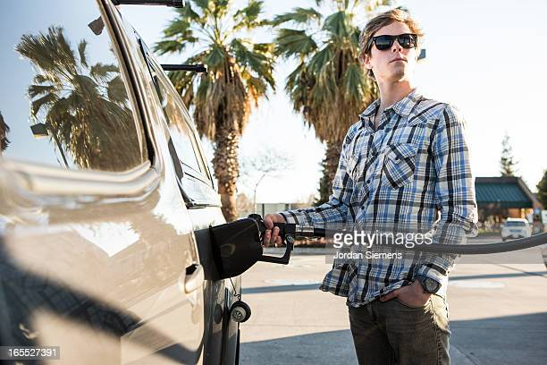 A man pumping gas.