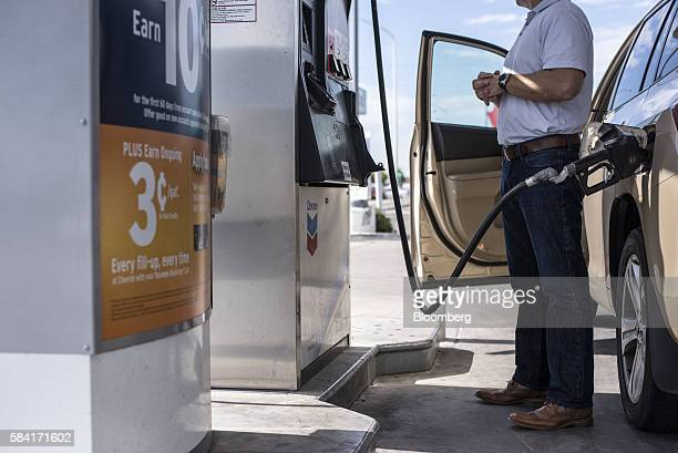 A man pumps gas into his car at a Chevron Corp gas station in Albuquerque New Mexico US on Tuesday July 26 2016 Chevron is scheduled to release...