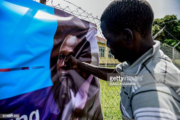 TOPSHOT A man punches a banner bearing a picture of former child soldierturnedwarlord Dominic Ongwen before the screening of the start of his ICC...