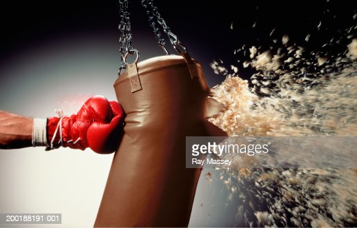 Man punching punch bag and stuffing exploding from bag