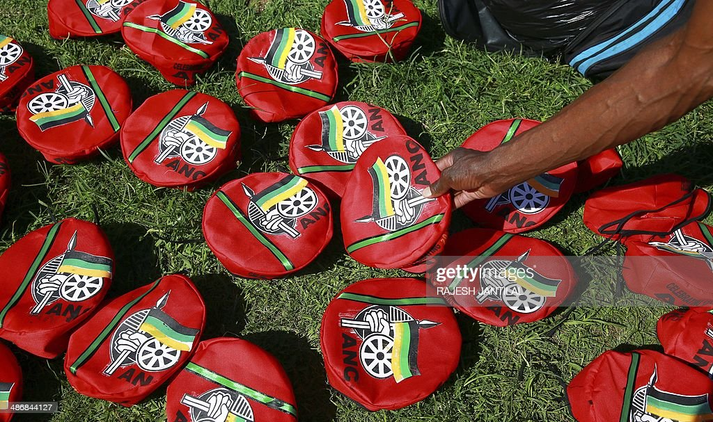 A man purchases a beret of the African National Congress (ANC) during a march organised by the Congress of South African Trade Unions (COSATU) to support the ruling ANC party in Durban, on April 26, 2014. COSATU (South Africa's largest trade union comprising of over 2 million workers) and the SACP are in a tripartite alliance with the ANC, and have declared their support to the ANC in the upcoming elections on May 7, 2014.