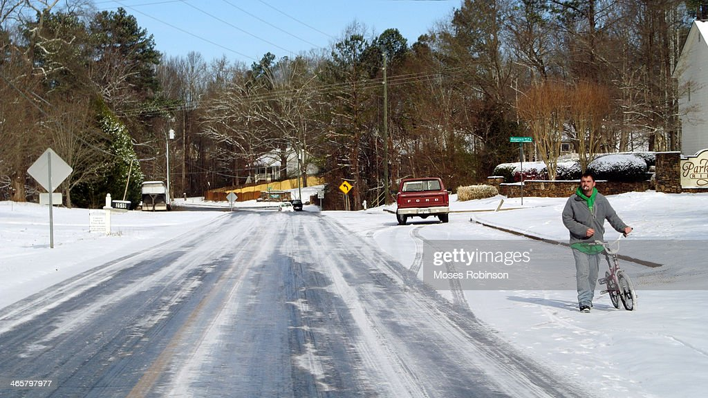 A man pushes a bike along ice-covered route 78 on January 29, 2014 in Snellville, Georgia. Thousands of motorists were stranded, many overnight, as a winter storm dropped three inches of snow, and ice made driving hazardous.