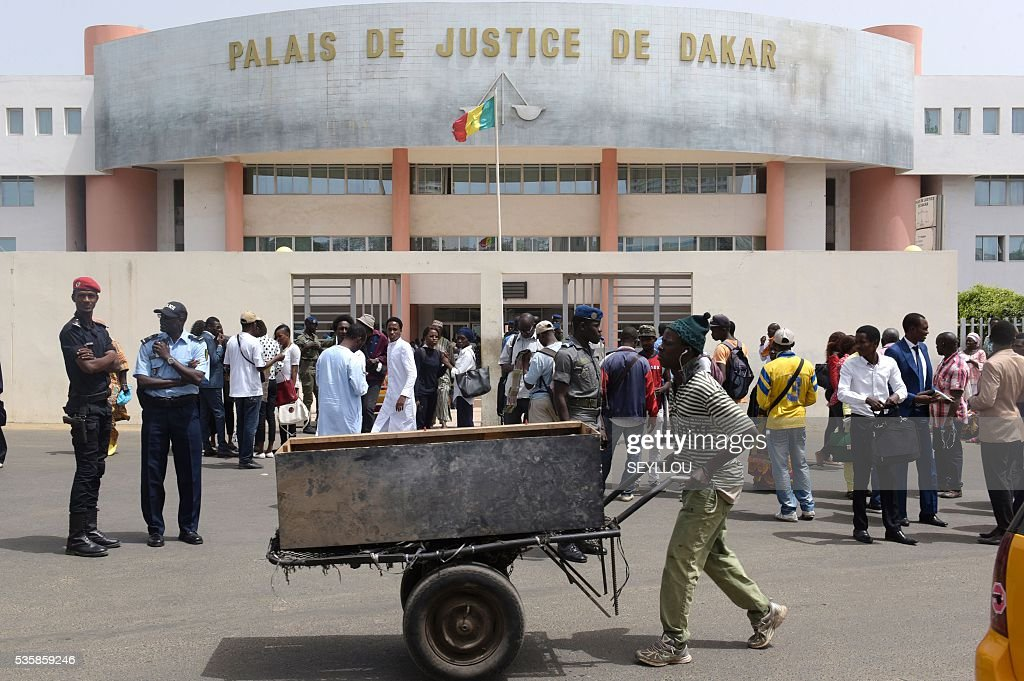 A man pushes a carriage past people and Senegalese security forces members standing outside Dakar Courthouse ahead of the sentencing of former Chadian dictator Hissene Habre on May 30, 2016 in the Senegalese capital. Former Chadian dictator Hissene Habre was found guilty of crimes against humanity and sentenced to life in prison by a special court in Senegal on May 30, 2016. The case, at the Extraordinary African Chambers (CAE) - a special tribunal set up by the African Union under a deal with Senegal - is the first time a country has prosecuted a former leader of another nation for rights abuses. / AFP / SEYLLOU
