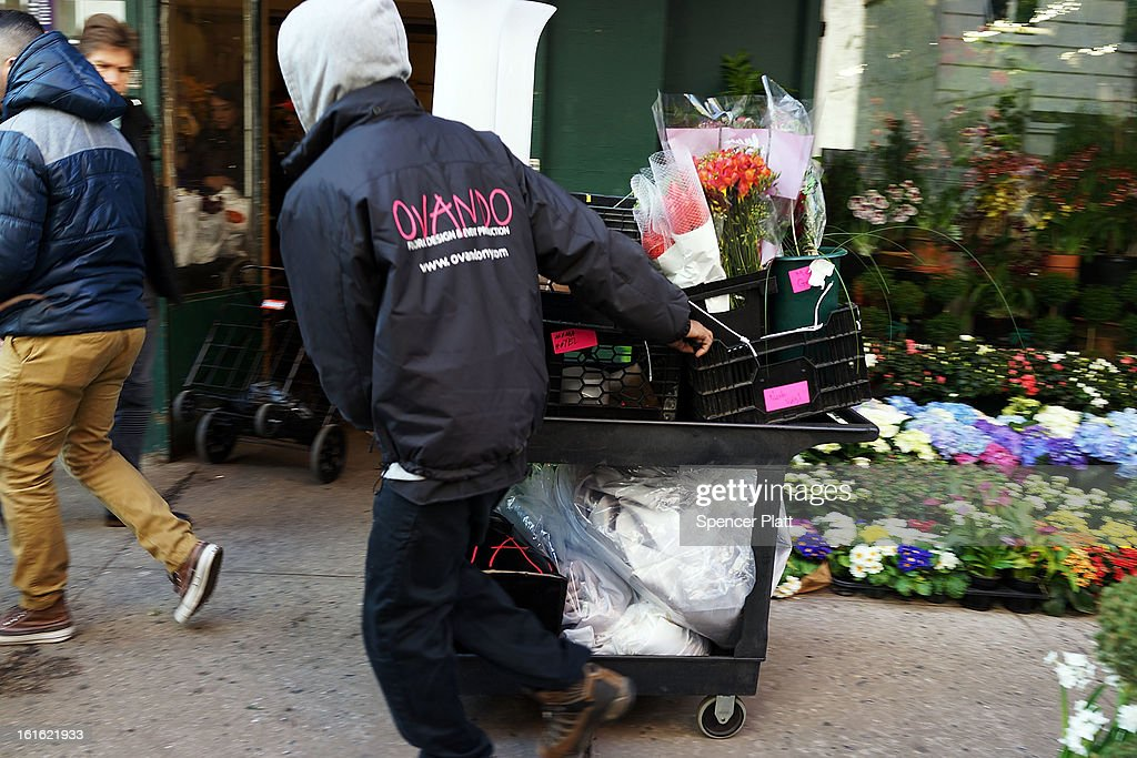 A man pushes a cart of flowers for delivery in the floral district on February 13, 2013 in New York City. With Valentines Day tomorrow, the district is experiencing a rush of floral buyers and sellers to service customers on the national day of romance. Along with Mother's Day, Valentine's Day is one of the busiest days of the year for florists and flower growers.