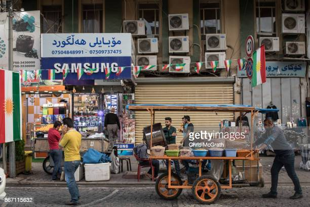 A man pushes a cart past a Kurdish flag at a market in the old city on October 27 2017 in Erbil Iraq After the Kurdish Regional Government held an...