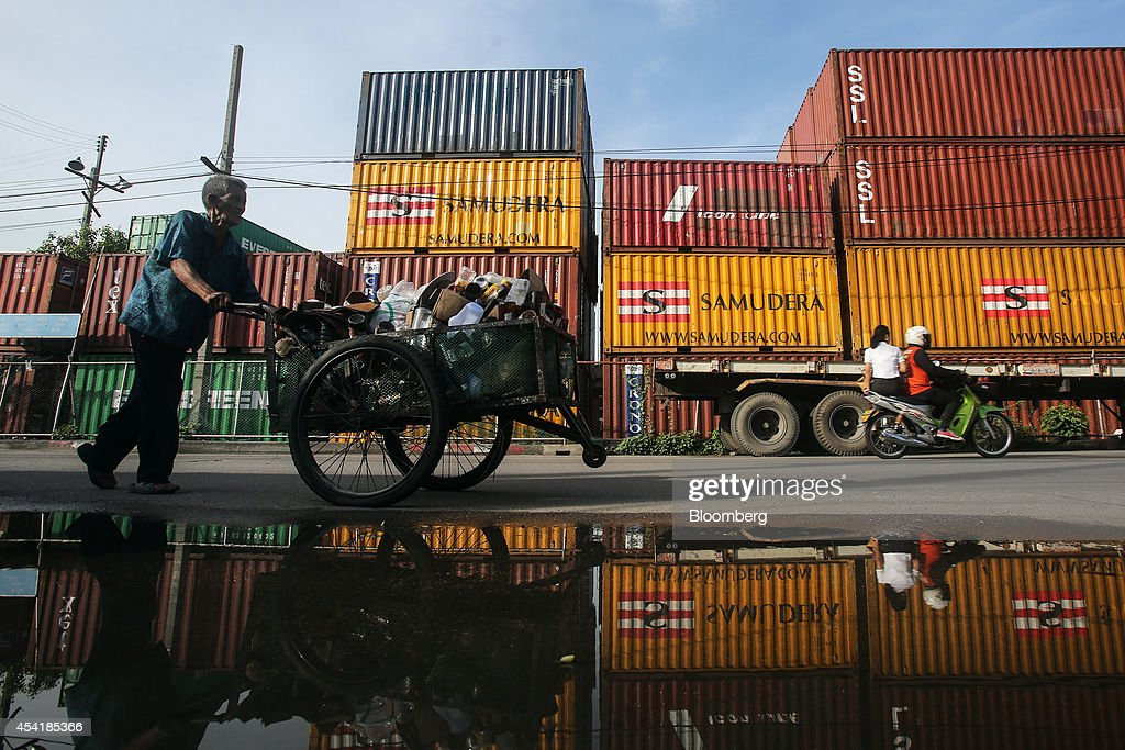 A man pushes a cart past stacked containers at the Custom Global Service Co. container depot in Bangkok, Thailand, on Monday, Aug. 25, 2014. Thailand's trade figures are scheduled for release on Aug. 27. Photographer: Dario Pignatelli/Bloomberg via Getty Images