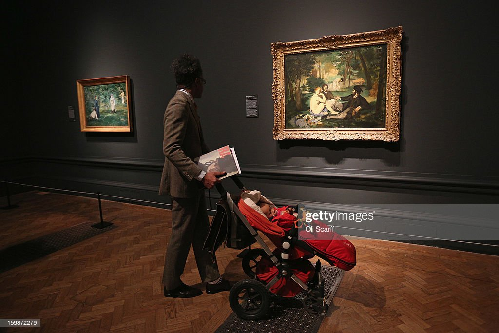 A man pushes a child in a pram past a painting by Edouard Manet entitled 'Dejeuner sur l'herbe' (R) in the Royal Academy of Arts on January 22, 2013 in London, England. The painting features in the Royal Academy's new exhibition 'Manet: Portraying Life' which displays over 50 paintings spanning his career. The exhibition open to the general public on January 26, 2013 and runs until April 14, 2013.