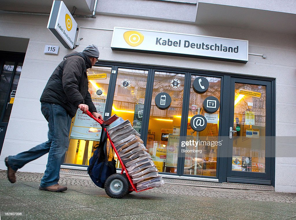 A man pushes a delivery cart past a Kabel Deutschland store, operated by Kabel Deutschland Holding AG, the German cable operator in Berlin, Germany, on Friday, March 1, 2013. Vodafone Group Plc has put on hold plans to approach Kabel Deutschland Holding AG about a takeover bid after leaks of a potential offer complicated internal discussions, according to three people familiar with the matter. Photographer: Krisztian Bocsi/Bloomberg via Getty Images