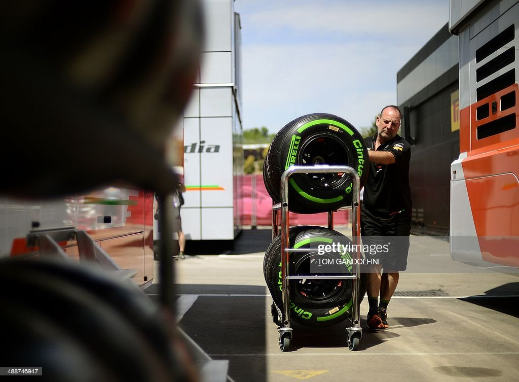 A man pushes a rack of tyres at the Circuit de Catalunya in Montmelo, on the outskirts of Barcelona on May 8, 2014, ahead of the Spanish Formula One Grand Prix.