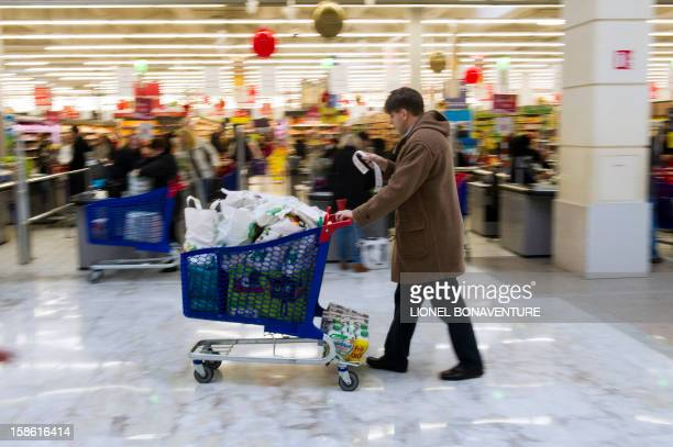 A man pushes a shopping cart after doing his grocery shopping in a supermarket on December 21 2012 in Montesson near Paris a few days ahead of...