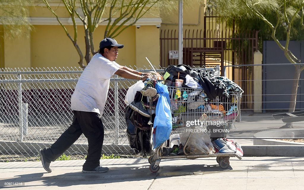 A man pushes a shopping cart full of belongings along a street in Los Angeles, California on February 9, 2016. Los Angeles City and County officials are voting February 9 on plans aimed at ending homelessness in the community, mostly by making permanent housing available to the tens of thousands of people who are homeless. / AFP / Frederic J. BROWN