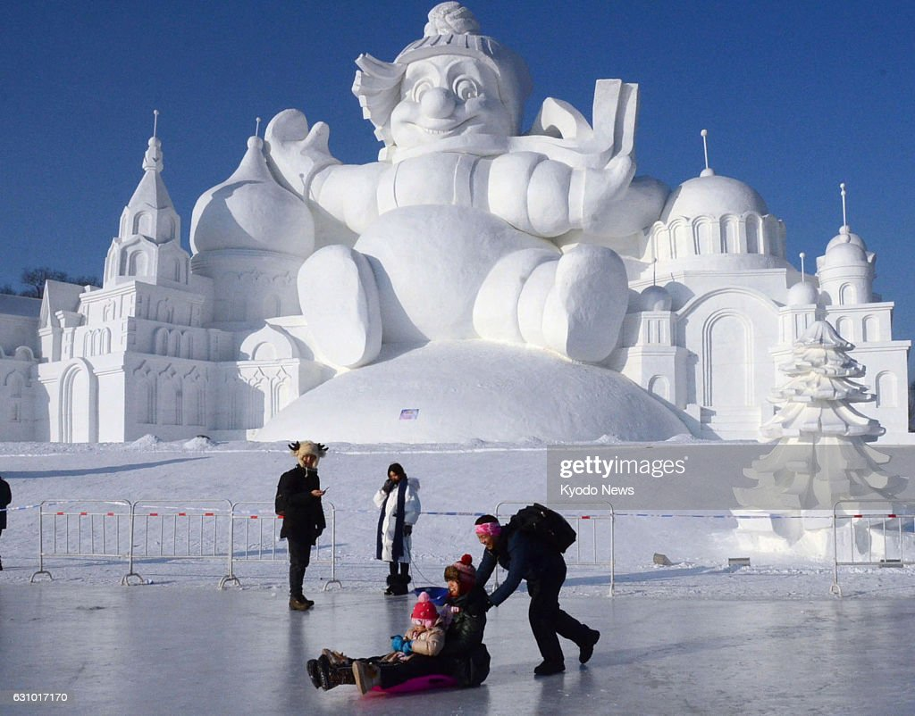 A man pushes a sled carrying a child in front of a large snow structure in Harbin, the capital of China's northeastern Heilongjiang Province, on Jan. 5, 2017, the opening day of an annual snow and ice festival that will run until the end of February.