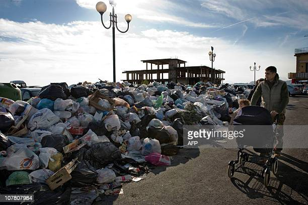 A man pushes a stroller as he walks past uncollected garbage in Pozzuoli 10 Km from the city of Naples on December 29 2010 Firefighters in the...