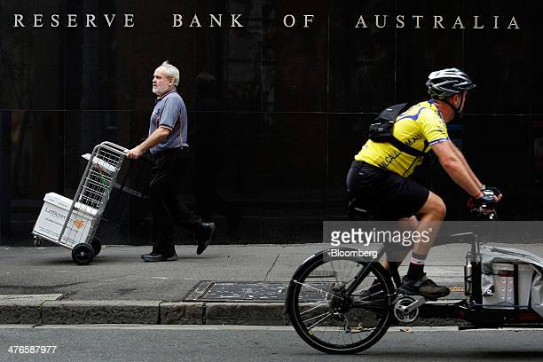 A man pushes a trolley as a courier cycles past the Reserve Bank of Australia headquarters in the central business district of Sydney Australia on...