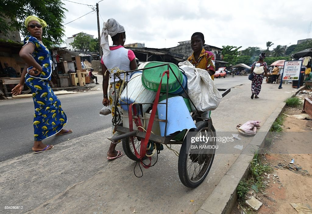 A man pushes a trolley with plastic waste used to fabricate cobblestone at a waste repurposing facility on May 23, 2016 in Attecoube, in Abidjan. / AFP / Sia KAMBOU