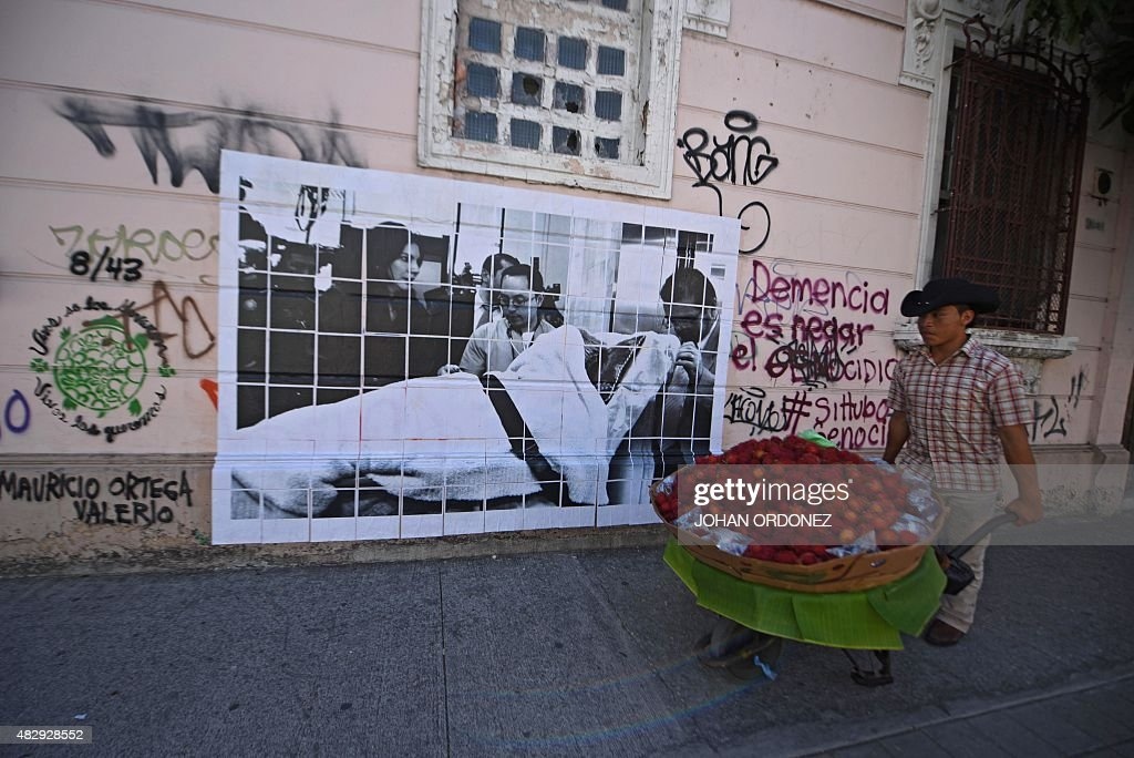 A man pushes a wheelbarrow as he walks in front of a picture showing former Guatemalan dictator Jose Efrain Rios Montt on a trolley next to his...
