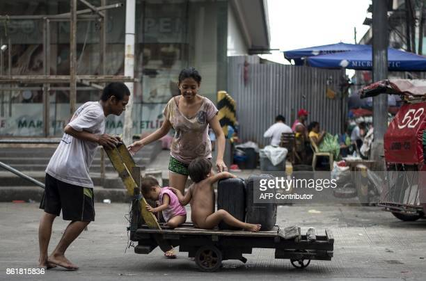 TOPSHOT A man pushes a wooden cart with jerrycans and his children in Manila on October 16 2017 / AFP PHOTO / NOEL CELIS