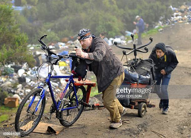 A man pushes his belongings out of a Silicon Valley homeless encampment known as The Jungle on December 4 in San Jose California Authorities began...