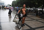 A man pushes his bicycle on a street in Beijing on July 19 2016 / AFP / GREG BAKER