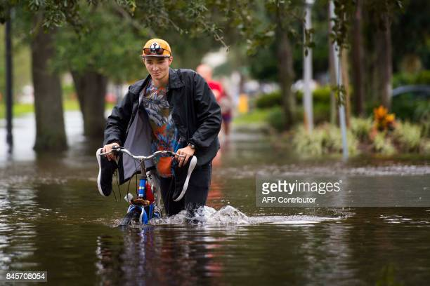 A man pushes his bicycle through the flooded streets of the San Marco historic district of Jacksonville Florida on September 11 after storm surge...