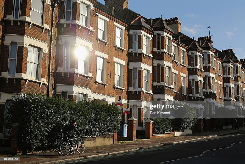 A man pushes his bike past a row of houses near Battersea on January 30, 2013 in London, England. According to a report from independent analysts Oxford Economics, the average mortgage deposit for first-time buyers in London, is likely to exceed £100,000 GBP by 2020.