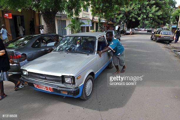 A man pushes his car in the centre of Conakry on May 31 2008 where most service stations were still closed down after looting earlier in the week...