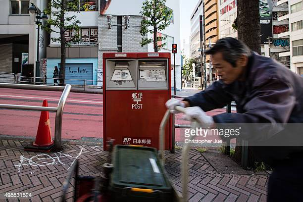 A man pushes his crate of tools past a Japan Post mailbox in downtown Tokyo on November 4 2015 in Tokyo Japan Shares in Japan Post with its banking...