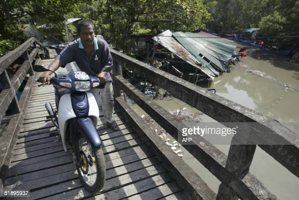 A man pushes his motorcycle over a bridge in the fishing village of Balik Pulau Penang 27 December 2004 The fishing village was the hardesthit area...