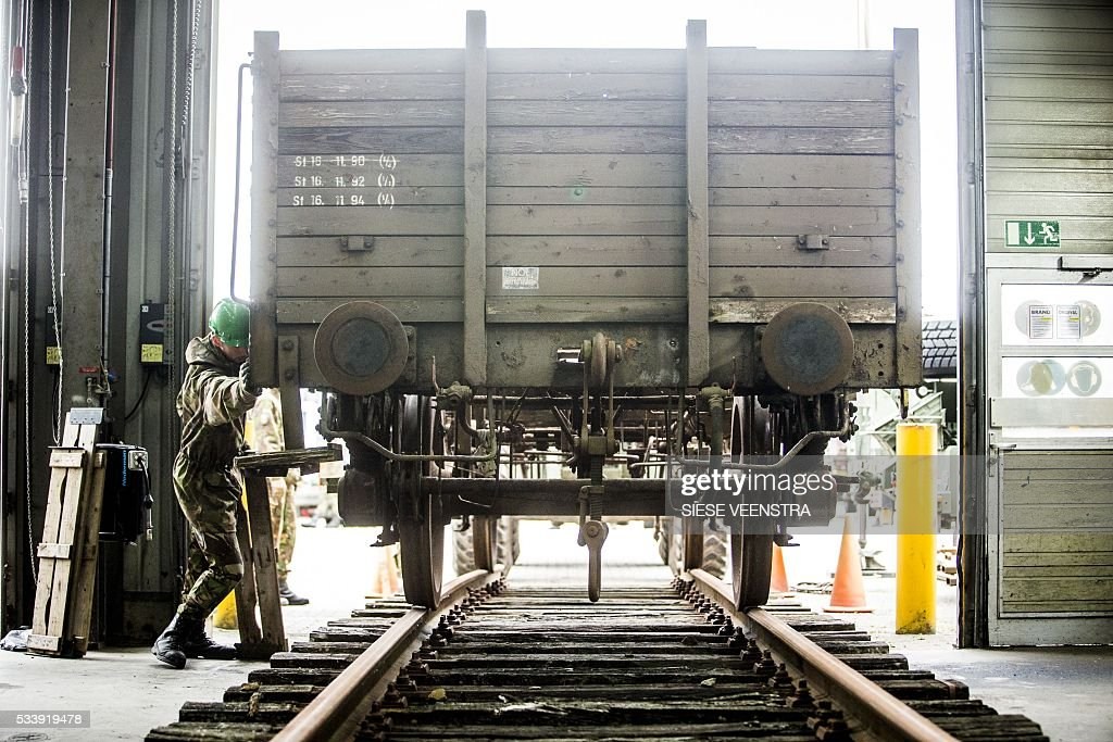 A man pushes one of the three old freight waggons that are brought to The Memorial Centre Camp of Westerbork in Coevorden on May 24, 2016. The three old freight waggons have probably been used for the deportation of Jews and Romanis during the Second World War. / AFP / ANP / Siese Veenstra / Netherlands OUT
