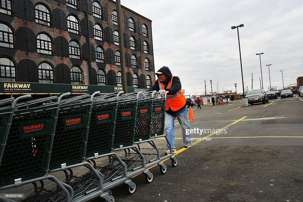 A man pushes shopping carts by the building housing the newly re-opened Fairway Market on the waterfront in Red Hook on March 1, 2013 in the Brooklyn borough of New York City. Fairway, which quickly became a popular shopping destination and an anchor in the struggling community of Red Hook, was closed following severe flooding during Hurricane Sandy on October 29, 2012. Like the rest of Red Hook, Fairway has struggled to quickly re-open in a neighborhood that lost dozens of businesses during the storm. The re-opening, which included a ceremony and ribbon cutting featuring Miss America and Mayor Michael Bloomberg, is being trumpeted as the Red Hook neighborhood's official comeback since the storm.
