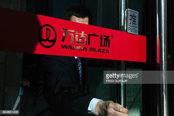 A man pushes the door at the entrance of the Chinese conglomerate Wanda Group building in Beijing on January 12 2016 Chinese conglomerate Wanda Group...