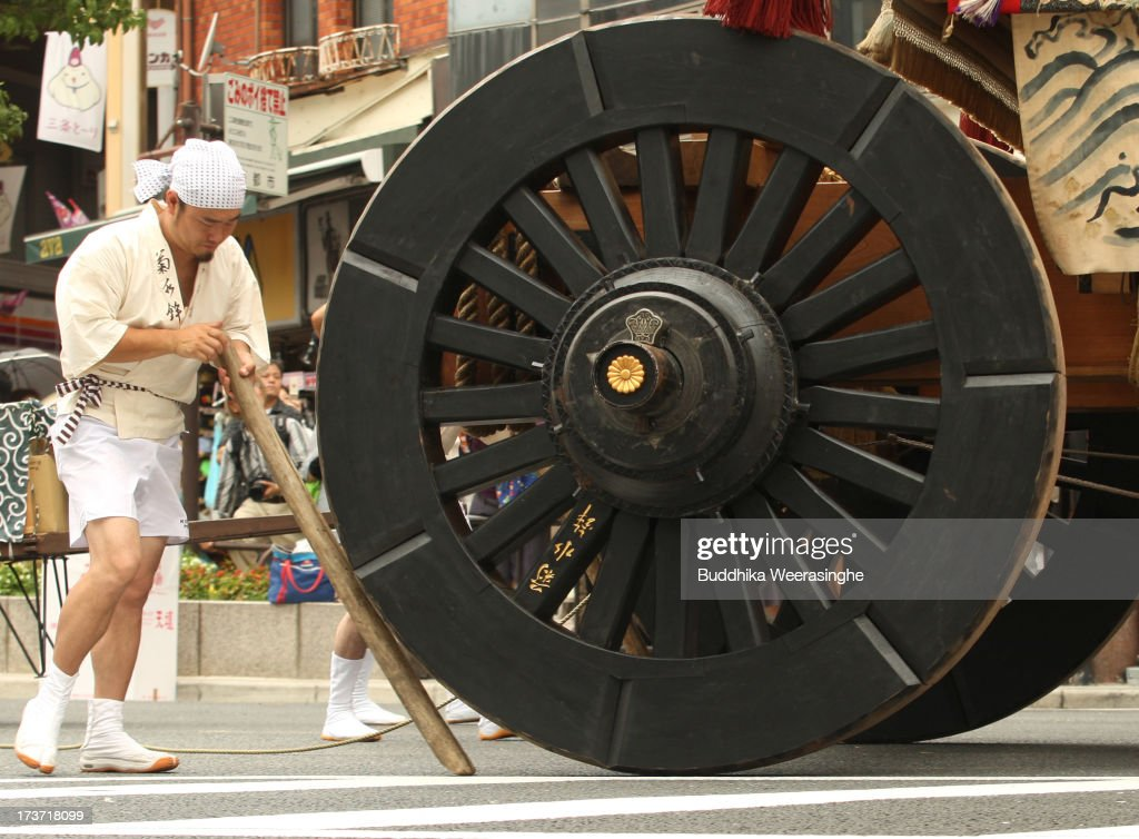A man pushes weel of float named Yamahoko during the annual Kyoto Gion Festival on July 17, 2013 in Kyoto, Japan. The Gion festival is one of three biggest Japanese festivals. dating back to the 9th century, the festival is part of a ritual intended to satisfy the Gods that brought on fire, floods and earthquakes. During the festival the streets are decorated with lanterns and many of the women dress in 'yukata', summer kimonos.