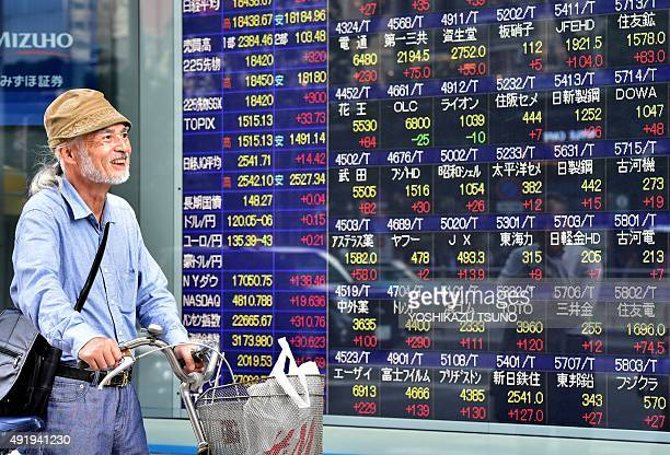 A man pushing a bicycle walks past a share prices board illustrating stocks on the Tokyo Stock Exchange in Tokyo on October 9 2015 Tokyo stocks ended...