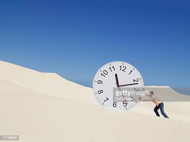 A man pushing a clock in the desert